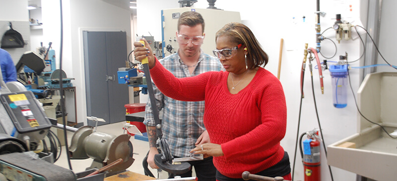 Woman learning to work with metal