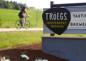 Woman Biking Past Tröegs Independent Brewing Sign